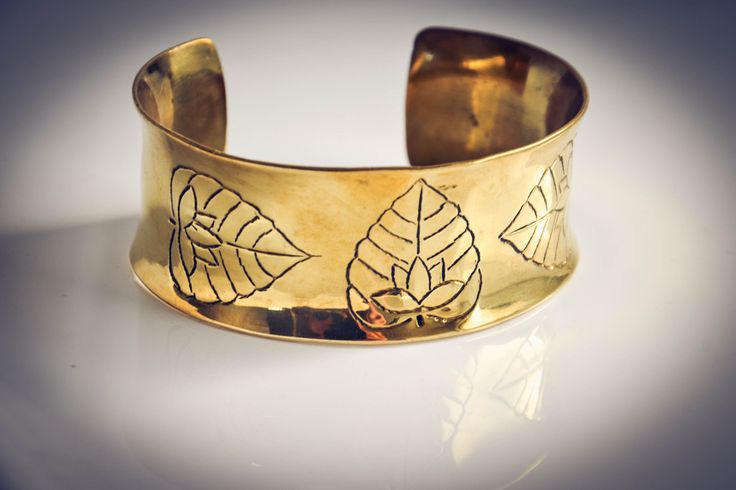 Hand carved cuff with lotus leaf and flower design.    Part of our artisan jewellery 'Gold' collection which is handmade by a local artisan in Siem Reap, Cambodia from recycled brass bullet shells.  Available now at www.banteaysreyboutique.com