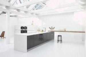Moderne keuken van Barletti in zwart en wit. Hoogglans is al een tijd een grote trend in de keuken. Al kiezen de meeste mensen voor een witte variant. In deze keuken is gekozen voor zwart hoogglans, wat een bijzonder luxe effect heeft. Haakt op het kookeiland ligt een brede houten werkblad. Hieraan kun je heerlijk ontbijten. De wit geschilderde balken en de vele ramen in het schuine dak zorgen ervoor dat de ruimte baadt in het licht.
