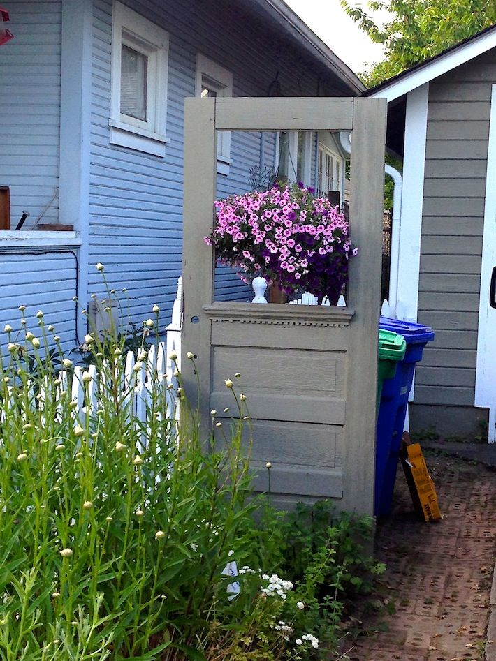 Repurposed vintage door cleverly hides trash cans