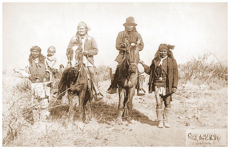 Scene in Geronimo's camp...before surrender to General Crook, March 27, 1886- Geronimo and Naiche mounted; Geronimo's son (Perico) standing at his side holding baby. Photo by C.S.Fly.