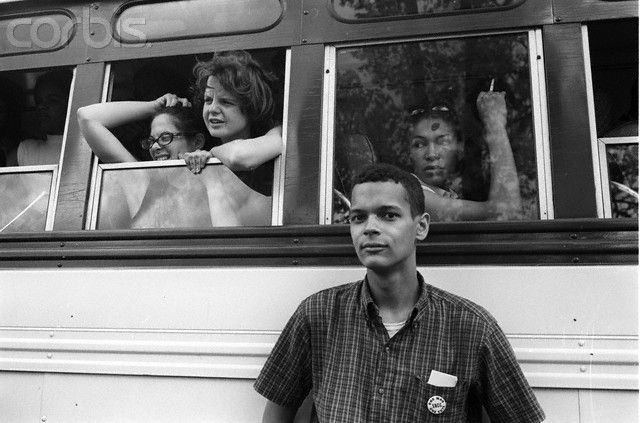 """Civil Rights Activist Julian Bond  Civil rights activist Julian Bond stands next to a bus full of young people taking part in the Congress of Racial Equality (CORE) training session. The session then allowed them to participate in the """"Freedom Summer"""" campaign, which registered new voters in the Deep South.    © Steve Schapiro/Corbis"""