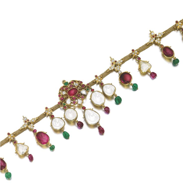 Ruby, emerald and diamond necklace. Set with a fringe of cabochon rubies and flat-cut diamonds, suspending polished emerald and ruby beads, the central foliate plaque set with a cabochon ruby and facetted rubies, emeralds and diamonds, on a modern cordette.