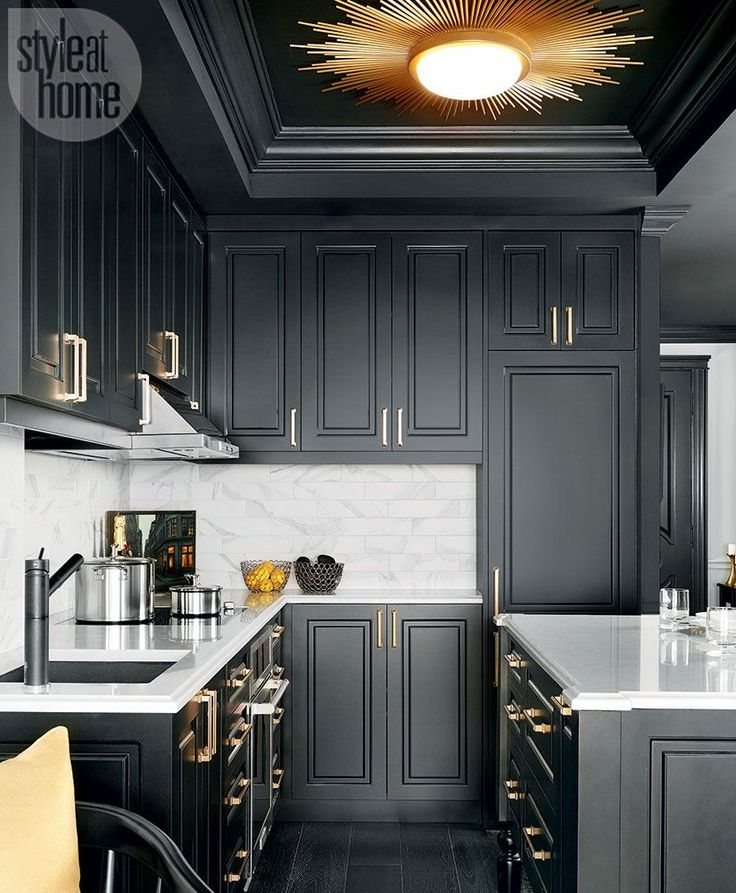 Dignified and dramatic, the black kitchen is accented with satin brass pulls, a black granite sink and a gold-hued sunburst light fixture