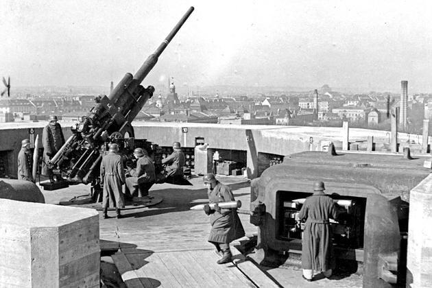 FLAK torens Berlijn - De grote 128mm-Flak Zwilling 40-kanonnen vuren met elke loop 10 à 12 granaten per minuut af. Het kanon kan dus in totaal 20 tot 24 granaten per minuut afvuren, afhankelijk van de snelheid waarmee de bemanning de munitie aanvoert. Bereik 14 km hoog.