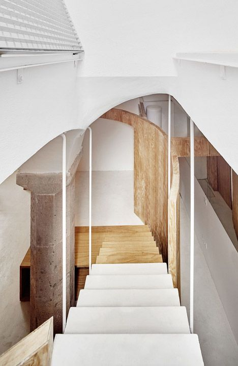 Architect Raúl Sánchez has converted the vaulted basement of a Barcelona house into a subterranean apartment, with rooms separated by a curving pine partition