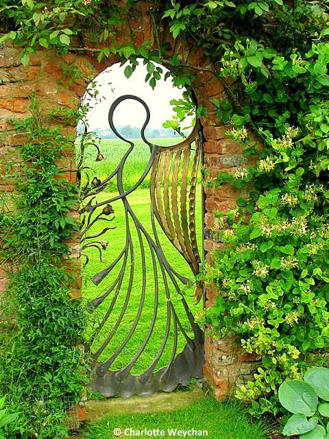 Garden gate - the angel - photo by Charlotte Weychan. At Birtsmorton Court - UK. Gate by blacksmith Michael Roberts --- *Note the honeysuckle to the right. Hmmmmm More