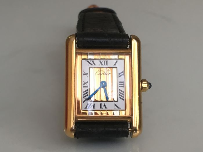 Cartier Tank Vermeil Trinity 3 Gold - Ladies Watch - 1980s  Offering a nice and rare Cartier Tank Vermeil model with Trinity dial which has 3 golden lines Rosegold Yellowgold and Whitegold. The case is 0.925 silver with gold plating in good condition. The movement is a quartz Cal. 66 running perfectly. The case measures 22x28mm without crown. The watch is fitted with a used black leather strap. Reference number is 3 66001 and it is Cartiers one most of the iconic models. The watch is fully…