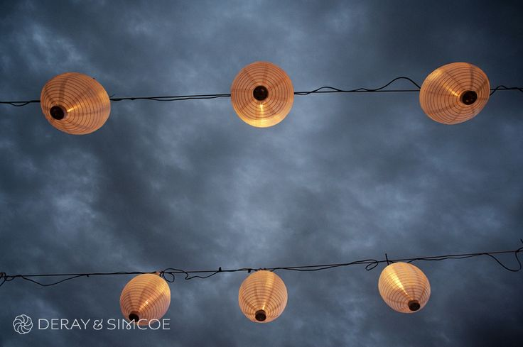 Paper lanterns hanging in the moody blue night sky. Wedding reception styling, ideas and inspiration.  Reception Venue: The Quarry Amphitheatre Photography by DeRay & Simcoe