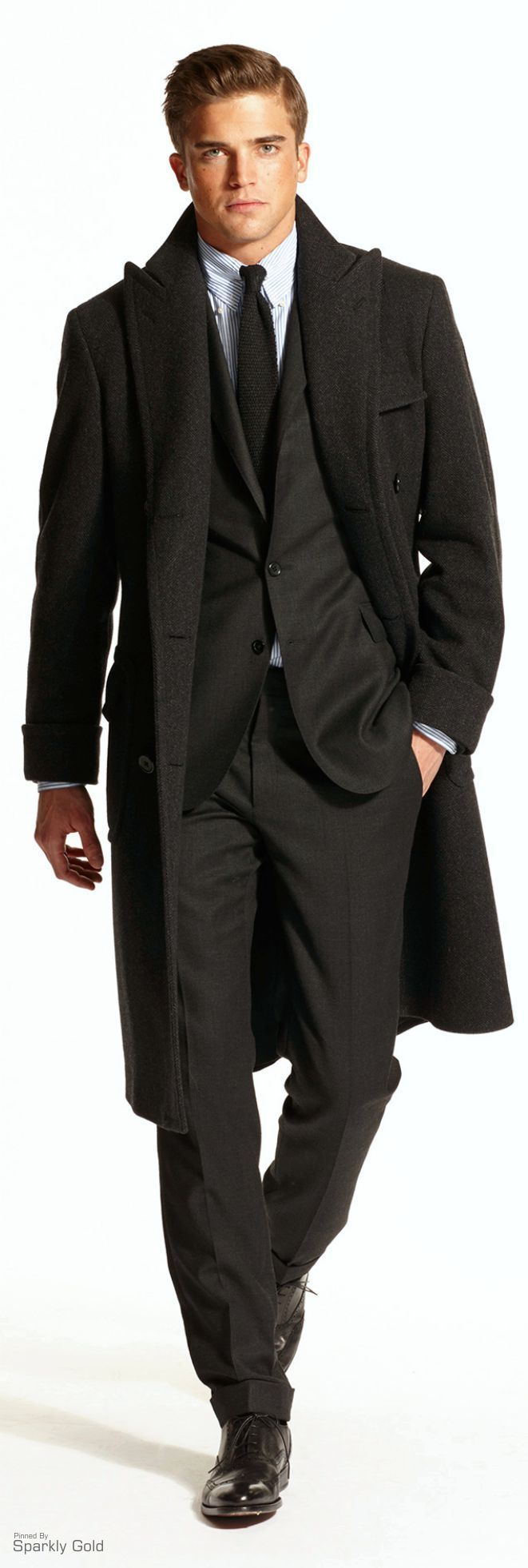 I like this overcoat quite a bit, and the suit underneath is a nice deep charcoal. The shirt & tie combo is a bit weird looking, but overall quite a very good look