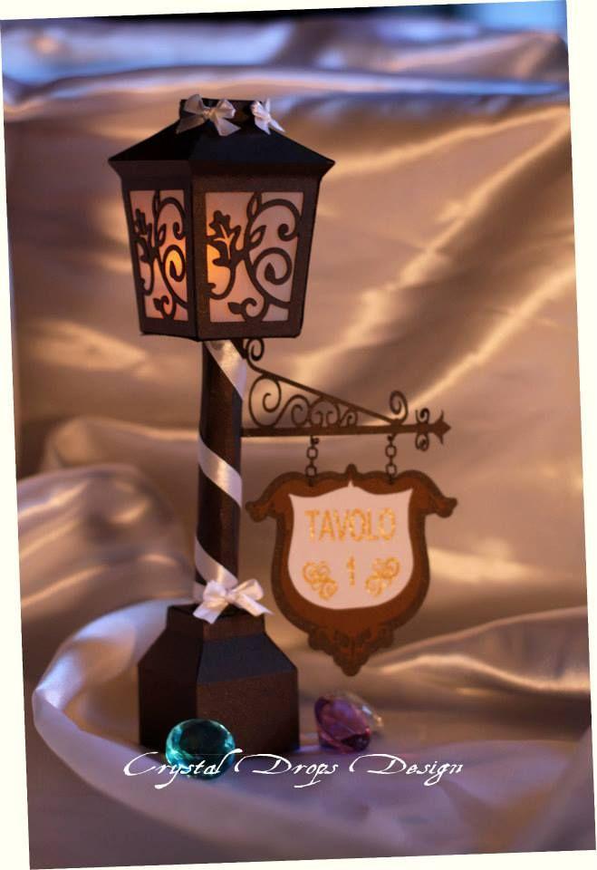 """Lampioncino segnatavolo (con illuminazione """"tea light"""") intagliato in pregiata carta perlescente nera.  L'effetto di trasparenza è stato creato con traslucida bianca. La tag riporta una scritta in oro.   Rifinito con nastro doppio raso.   Delizioso vero?"""