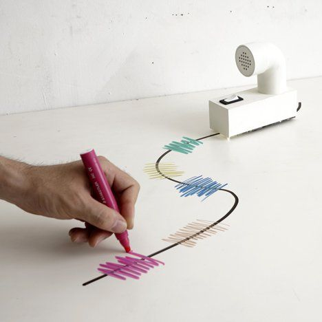 Miniature mobile robots move along a line-drawn circuit and turn colour into music by Japanese designer Yuri Suzuki.