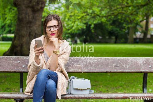 Young woman sitting in the park with phone