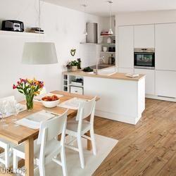 W małym mieszkaniu właściciele wykorzystali każdy skrawek przestrzeni. Kuchnia z salonem tworzy jedno wnętrze, by optycznie powiększyć mieszkanie. W aranżacji kuchni wybrali jasne kolory oraz proste meble. W kuchni zdecydowano się na białe meble zrobione na wymiar.