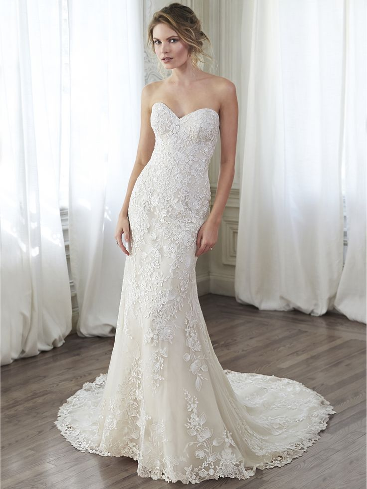 Maggie Sottero - ARLYN, This lace slim A-line gown channels timeless elegance with its classic sweetheart neckline, cascading floral lace appliqués, and lace-trimmed hemline. Finished with corset closure.