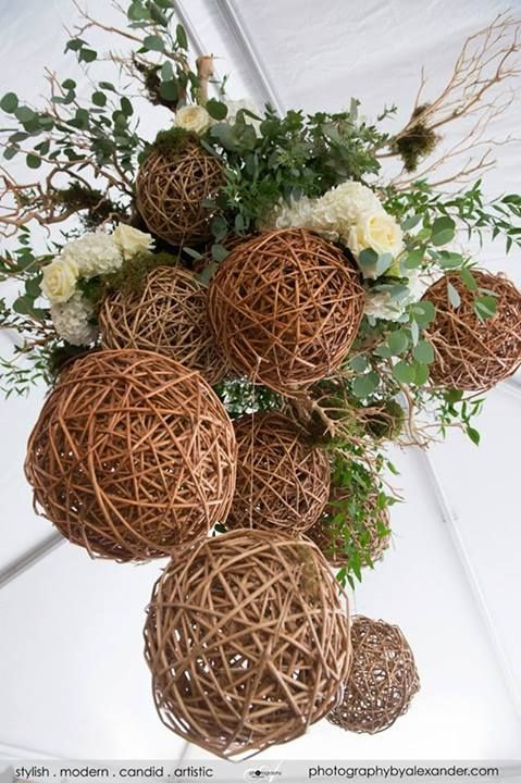 A closer view, this eco-chic chandelier is made with hanging wooden and moss balls from a manzanita branch base. www.Intrigue-designs.com then covered it in silver dollar eucalyptus, willow branches, grasses, and white roses. It is the perfect centerpiece for any rustic or eco-chic wedding/event at any venue or tent. PHOTO www.photographybyalexander.com