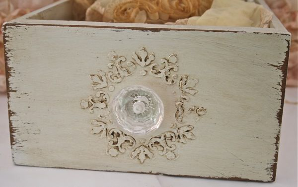 The last drawer was also painted with Heirloom white paint. she used a stencil and vinyl spackle to apply the raised pattern to the front and side of the box.
