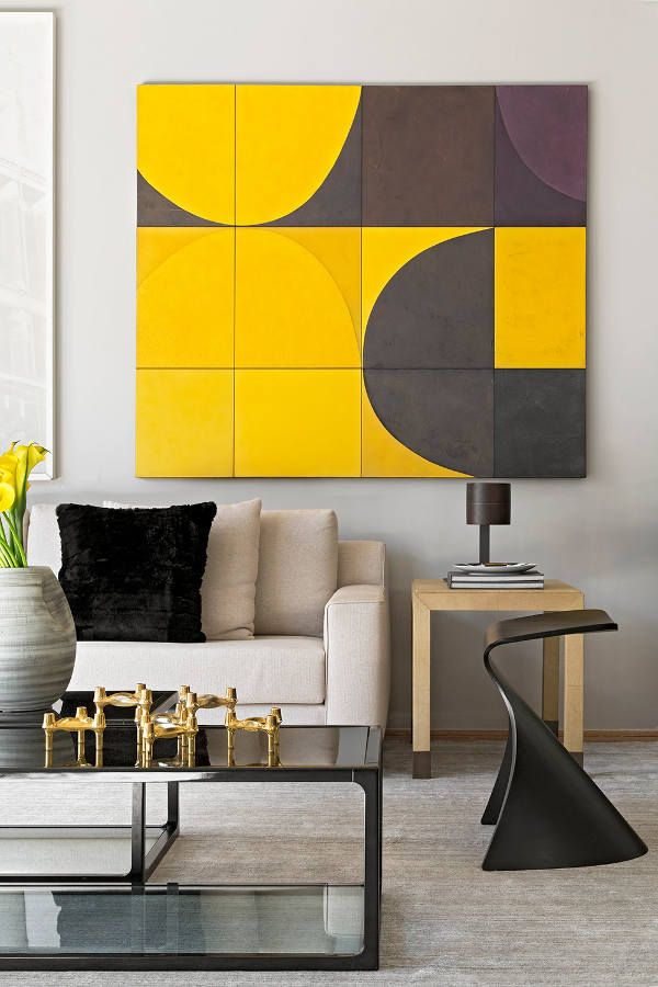 Close up of yellow and grey painting, with a pale wood side table and a neutral sofa. Black coffee table; gold accents to play up the yellow.