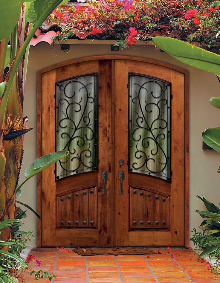 Beautiful Arch Top Double Entry Doors with Bellagio wrought iron design. The unique pattern on this Knotty Alder wood door adds rustic elegance to the home.