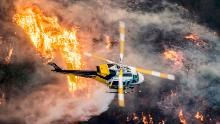 A Los Angeles County Fire helicopter flies over during the 'Skirball Fire' which began early morning in Bel-Air, California, USA, 06 December 2017. An outbreak of several fires North of Los Angeles has occurred as one of the strongest Santa Ana winds forecast of the season is ongoing and expected to last several days. EPA-EFE/JOHN CETRINO