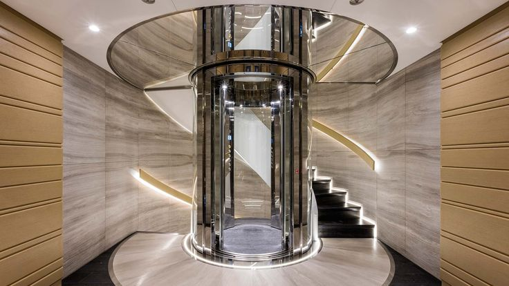 beautiful yacht interior staircase design.  Marble and wood craftsmanship with a sleek elevator at the center.    www.fm-arch.it