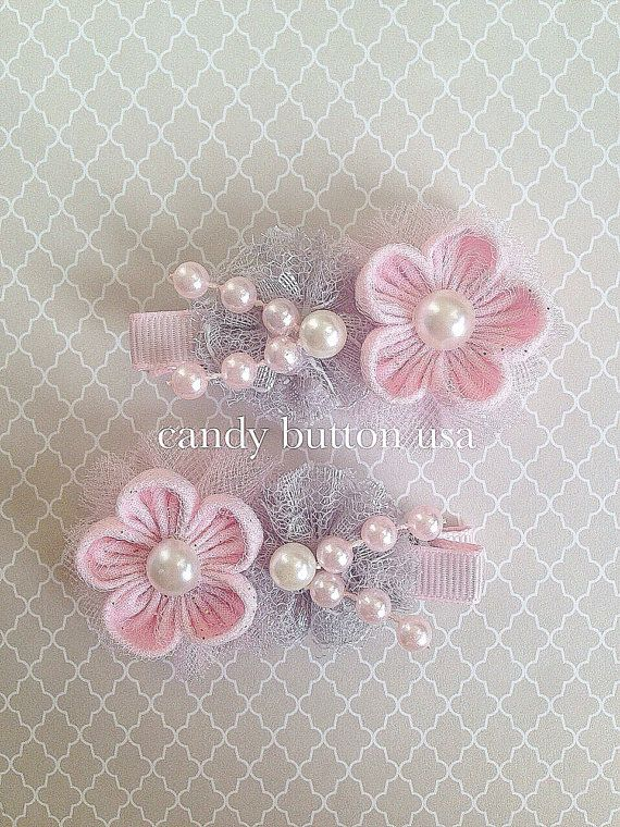 Dress your little princess with this cute handmade hairclips from CandyButtonUSA! This listing is for 1 pair only, please choose color from the dropdown box. First clip on the top is in ivory and bottom clip is in pink. Item sold as a pair. Partially lined hairclip measuring approximately 2 1/4 long adorned with handmade fabric flower, lace, tulle and synthetic pearls. This piece measures approximately 1 1/2 wide. *Please be aware there will be slight variations in each item due to its ha...