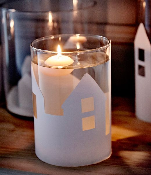 An IKEA CYLINDER vase is decorated with a paper cutouts of a winter landscape, filled with water and a floating candle.