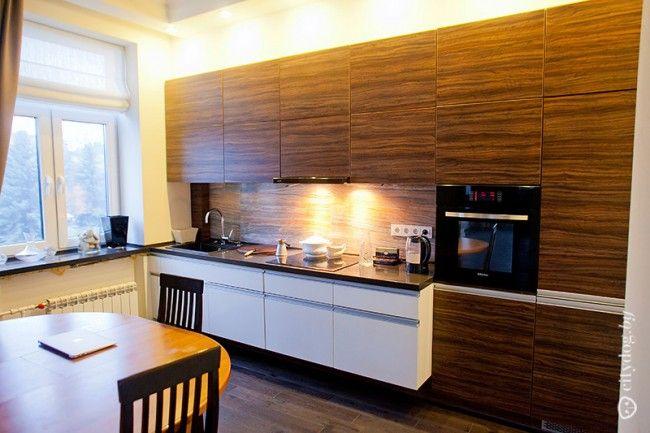 Современный дизайн прямой кухни-гостиной с фасадами под дерево и встроенной техникой