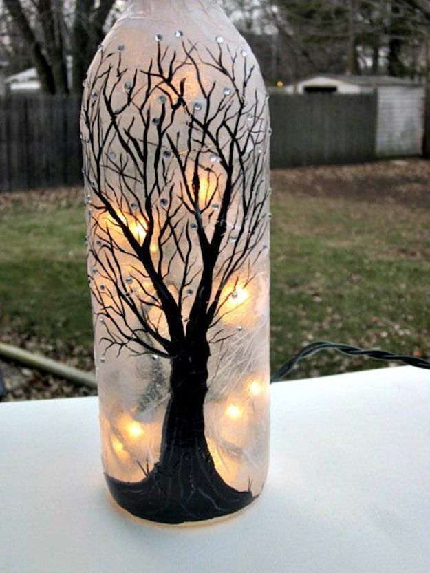Show off your artistic side with this hand painted centerpiece. Start off by coating a layer of frost paint on the bottle. Once dried, begin creating your tree. Add a few embellishments with a glue gun and sequins, and then finish off by placing some string lights inside.