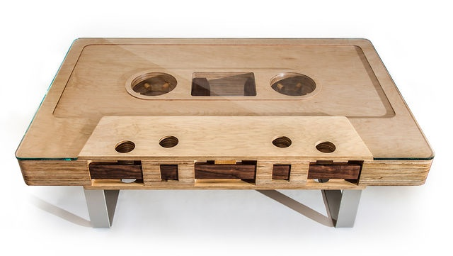 """The Mixtape Table — a 12:1 scale replica of a cassette tape — is now available. The Mixtape Table is made of high-grade Baltic Birch Plywood with maple veneer, solid American Walnut """"tape"""" throughout, and a hand-rubbed oil finish. Each coffee table is built to order, hand-assembled and finished in Seattle by the JSD team. The table is completely reversible - sides A and B, stamped and numbered on one side. The glass top is 3/8"""" with a polished edge. The whole table sits on a custom platform…"""