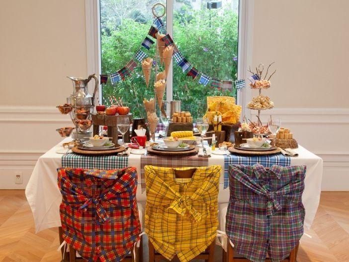 mesa junina com decoração de tecido e enfeites temáticos em azul, amarelo e vermelho.