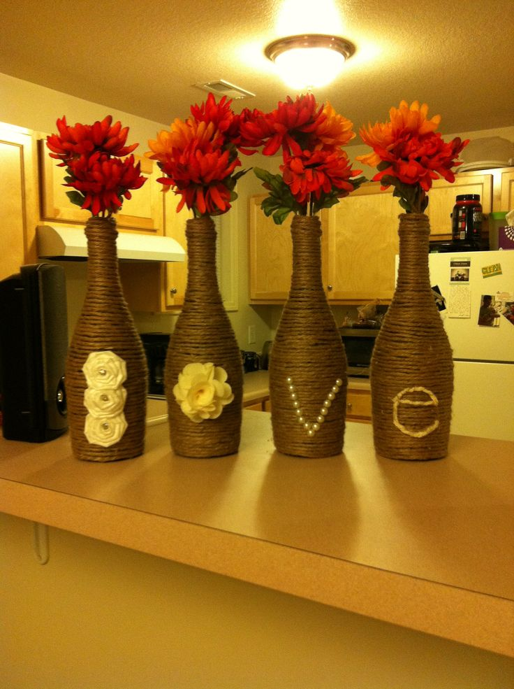 Wine bottles wrapped in twine using a hot glue gun. All of the supplies to spell out Love were bought in the scrapbook section of a craft store.