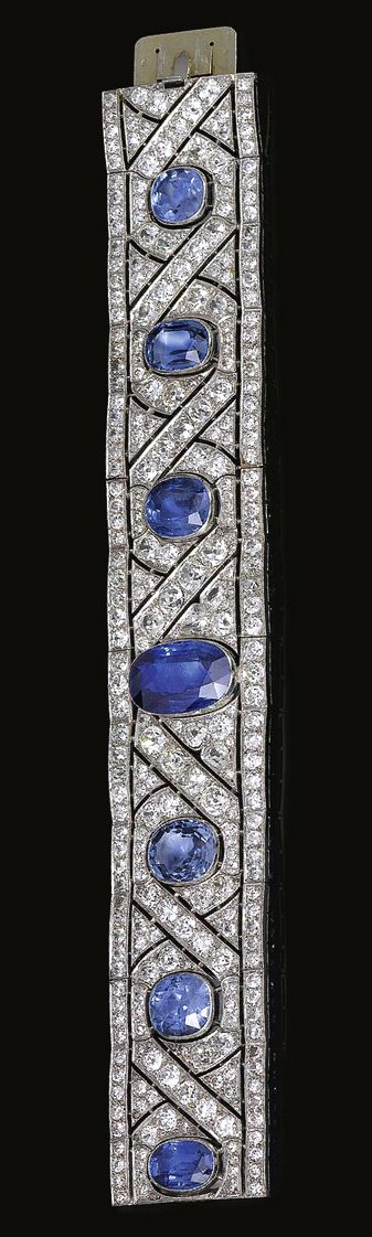 SAPPHIRE AND DIAMOND BRACELET, CHAUMET, CIRCA 1920 Of stylised ribbon and scroll design, millegrain-set with rose, circular- and single-cut diamonds, embellished with seven oval and cushion-shaped sapphires, mounted in platinum, length approximately 185mm, signed Chaumet et Cie Paris Londres, French assay and maker's marks.