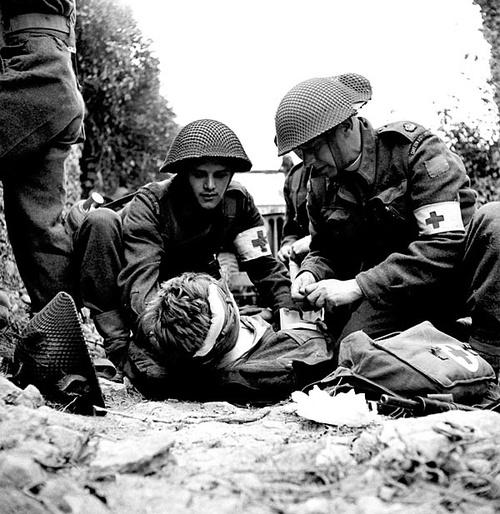 "According to the caption attached to this image, ""Canadian medics help a wounded soldier - Juno Beach, D-Day June 6th 1944."" Visuals such as this promote the idea that war doesn't only involve the 'killing' but the 'saving' as well."