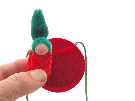 One Apple Doll Necklace Pip lives in his bright red apple, happy all the day long as your fellow traveler. He stands about 1-1/2 (4 cm) tall and is made from wood, cotton knit fabric. He is hand sewn and an easy companion. He can come out of the apple and is perfect to tuck into little spaces or yuck in your pocket. His face is hand drawn with permanent ink onto the cotton knit skin which covers the wood base of his head. His apple pocket is made from 100% wool felt and is strung on a 24...