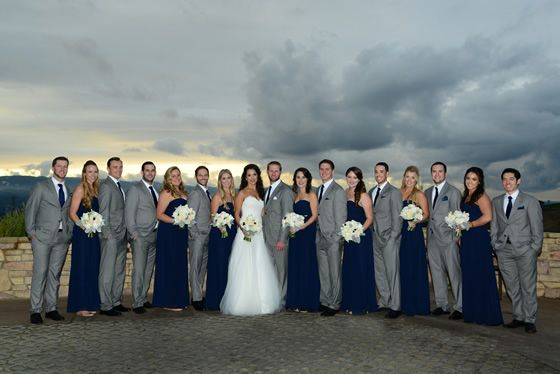 The navy bridesmaid dresses and grey groomsmen suits coordinate perfectly with the billowy clouds. Wedding Photographer: Carlos DaSilva Photography