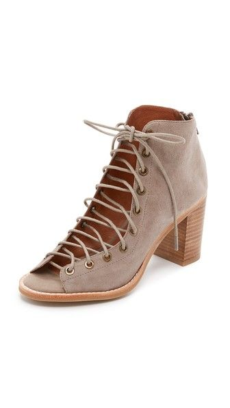 Luxe suede Jeffrey Campbell booties in an open-toe profile. Lace-up closure and exposed back zip. Stacked heel. Rubber sole.