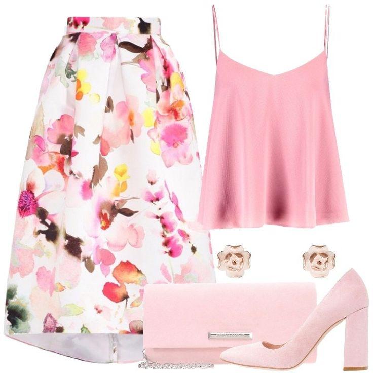 L'outfit è composto da una gonna lunga, un top con scollo a V profondo, da una pochette rosa, un paio di tacchi scamosciati e da un paio di orecchini.