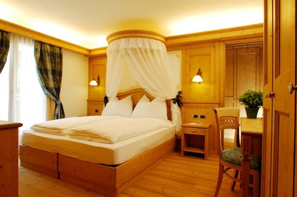 Suite Cima Sassara. Splendida suite adatta anche a famiglie; sono 2 camere comunicanti spaziose. Pavimento in legno naturale.    DOTATE DI:  Stanza 1:  - letto matrimoniale  - minibar  - TVColor, cassaforte  - ampio bagno con doccia e vasca idromassaggio    Stanza 2:  - salottino (o con 1/2 letti aggiunti)   - stufa  - TVColor, WI-FI  - balcone vista Dolomiti e Cima Sassara  - servizio con doccia.
