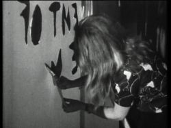 """Cutting('67-'68)- cinematic technique of """"cutting,"""" or editing, and its importance in the construction of filmic reality. A house is projected onto a paper screen and the window is cut with scissors. Next, Marshall McLuhan's sentence: """"The content of the writing is the speech"""" is cut out of the screen. Then, the naked body, serves as a living screen, the sign of which is shaved by the artist. The fellatio at the end shows the most direct form of communication which eschews words and images."""