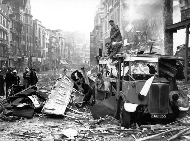The aftermath of bombing in London in 1940 can be seen above, with a group of men working together to clear up around a shattered bus