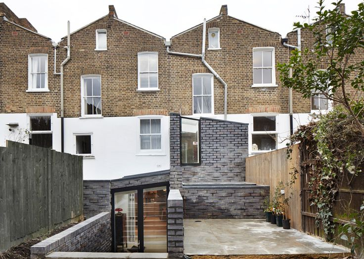 Slate-grey bricks applied in zigzagging rows give the walls of this London house extension a faceted texture