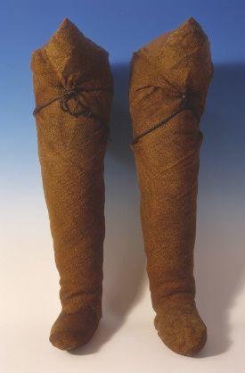 BOCKSTENSMANNENS HOSOR, FOTLAPPAR OCH ANDRA TYGLAPPAR  På benen bar mannen strumpor, eller hosor som det också kallas. De är också vävda av ull i tekniken treskaftad kypert.  Tyget i fötterna har bytts ut när det varit utslitet.  Hosorna är så långa att de når upp till låret och avslutas med en spetsig del. De har hållits uppe med läderremmar som har varit fastsatta på tre ställen. Remmen har varit till för att hålla hosorna uppe. De fästes alltså till ett bälte i midjan som satt under…