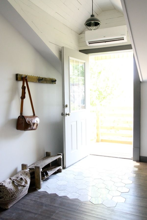 Clean white tiled entry transitioning into wood flooring catches light from the front door in modern converted warehouse apartment.