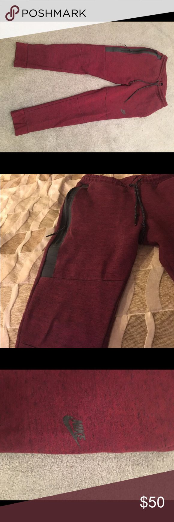 """Nike Joggers Men's dark red Nike Joggers.  Picture with pants on hanger is best representation of actual color.  Black zippers and Drawstring.  Note wear/slight damage on back right.  Purchased as Medium but washed and dried so they shrunk.  The waist from left to right is 14"""". The length from waist to bottom of pant is 36 1/2"""". Nike Pants Sweatpants & Joggers"""
