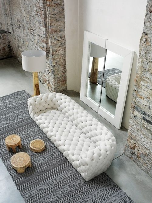 [CasaGiardino]  white tufted couch, split oversized mirror and stone walls...rough/luxe:
