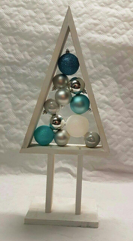 Kleine houten kerstboom,.wit, gevuld met kerstballen: blauwe, zilveren en witte