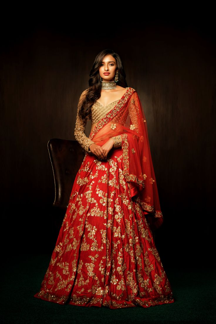 A sophisticated bias cut tango red lehenga , with a spray of floral peeta embroidery all over, is teamed with a champagne gold blouse. The blouse is completely done in zardosi with tulle fulle sleeves ornamented with zardosi florals. The look is completed with a red tulle dupatta with an ornamented velvet border