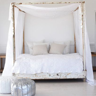 Reams of white fabric draped over distressed white painted bed frame creates a rustic yet chic all-white bedroom.