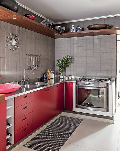 A cozinha projetada pelo arquiteto Gustavo Calazans segue o mesmo estilo do resto da decoração. Há, inclusive, a mesma prateleira de imbuia no alto, que guarda panelas e outros acessórios que não são usados no dia a dia