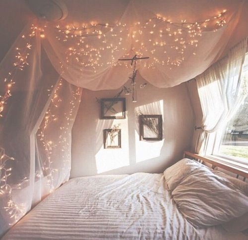 Such a beautiful contrast on light between the fairy lights and the positioning of the bed by the window.